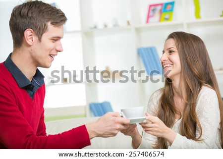 A young man brings his girlfriend coffee - stock photo