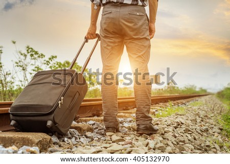 A young man carries a suitcase waiting for a train  - stock photo