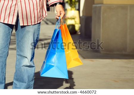 A young man carrying shopping bags at an outdoor mall - stock photo
