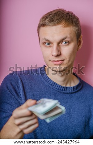 A young man close-up , gives or takes money. Dollars. Holds money in hands. . Photos