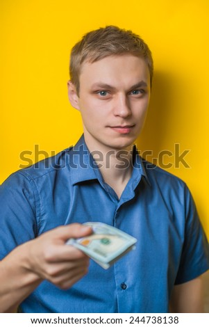 A young man close-up in a blue shirt on a yellow background, gives or takes money. Dollars. Holds money in hands. . Photos - stock photo
