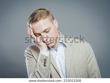 A young man close-up in a suit on a gray background, fall asleep. The guy wants to sleep. Gesture. Photos - stock photo