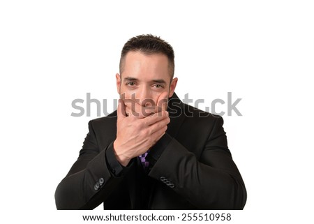 A young man covering his mouth in a speak no evil pose - stock photo