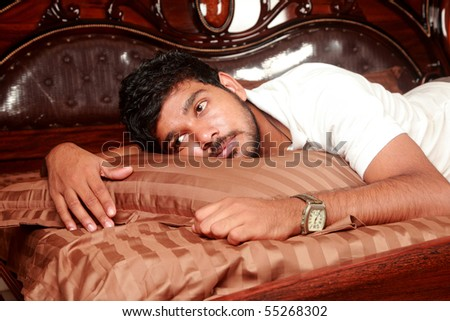 A young man day dreaming in bed - stock photo