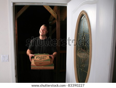a young man delivers fresh pizza to your door. Pizza Delivery Man. - stock photo
