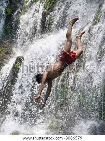 A young man dives off a waterfall makes it look like he is plunging to his death.