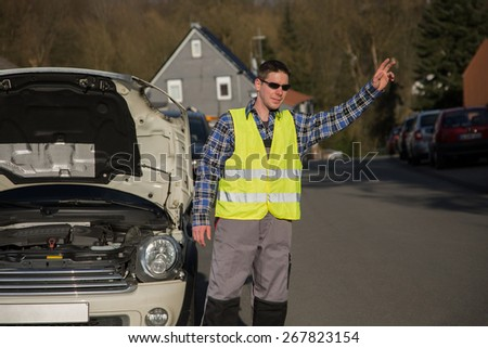 A young man dressed with an reflective vest is standing beside his car and ask for help with his hand. - stock photo