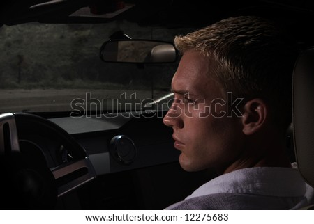 A young man driving a car at sundown