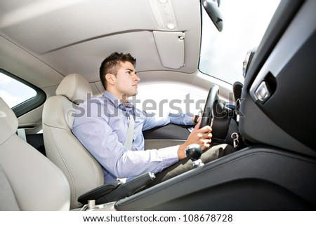 a young man driving the car - stock photo
