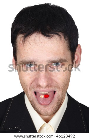 A young man eats a pill put it on the tongue - stock photo