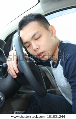 A young man falling asleep at the steering wheel - stock photo