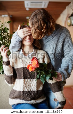 A young man giving bunch of red roses to his girlfriend while closing her eyes - stock photo