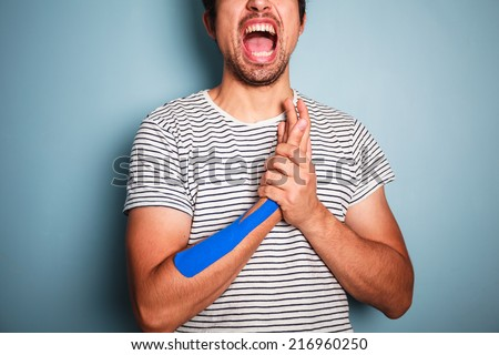 A young man has muscle pain and is wearing kinesio tape on his arm - stock photo