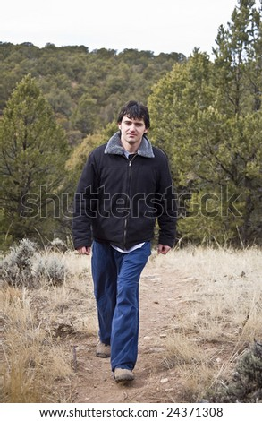 A young man hiking in the woods