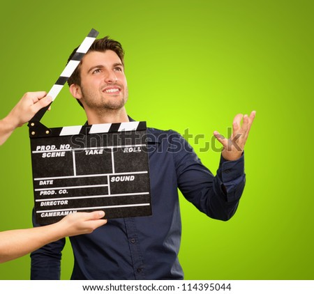 A Young Man Holding A Clapboard And Acting On White Background - stock photo