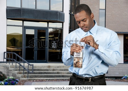 A young man holding a jar of money coins labeled retirement account - stock photo