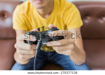 A young man holding game controller playing video games - stock photo