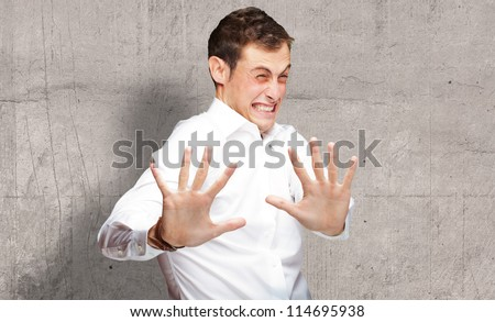 A Young Man Holding His Hands Out In Fear, Indoor - stock photo