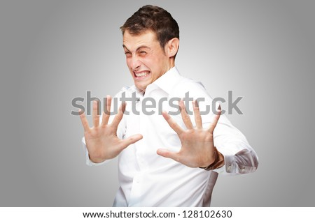 A Young Man Holding His Hands Out In Fear On Gray Background - stock photo