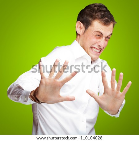 A Young Man Holding His Hands Out In Fear On Green  Background - stock photo