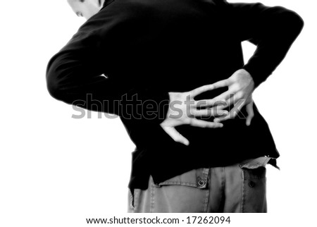 A young man holding his lower back in pain - stock photo