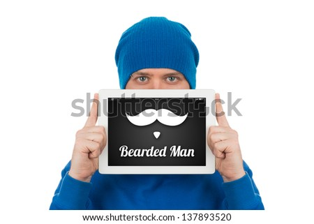 A young man holding in front of his face a tablet computer, on which are drawn a mustache and beard. You can put any inscription on the screen. - stock photo