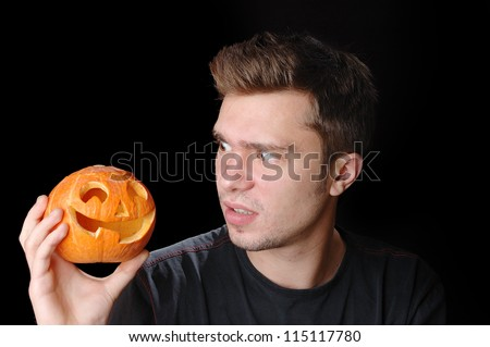 A young man holds his Halloween pumpkin - stock photo