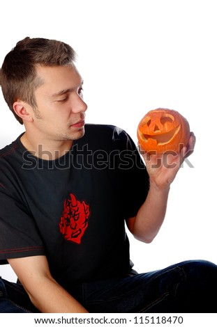 A young man holds his Halloween pumpkin.  Isolated on a white background - stock photo