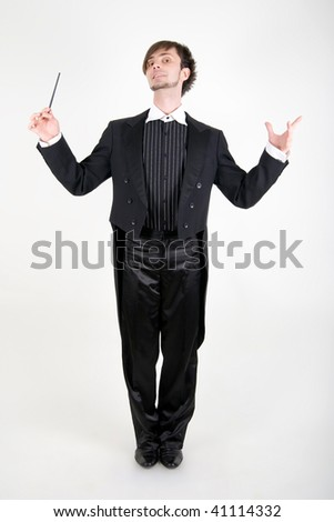 A young man in a black tailcoat is holding his hands and head up - stock photo