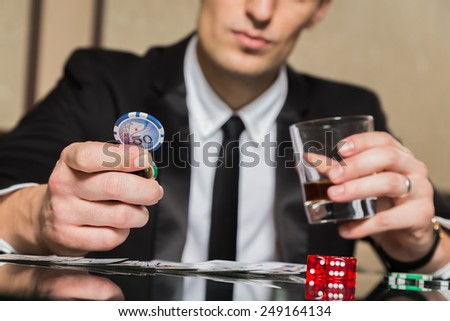 A young man in a business suit sitting at the poker table. Man gambles. The player at the gaming table playing cards. - stock photo