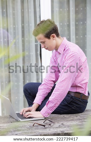 a young man in a red shirt sitting outside with a laptop