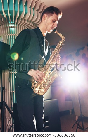 A young man in a suit playing on saxophone musical instrument. Saxophone instrument for jazz. Musician, saxophonist plays the saxophone music. Saxophonist with a saxophone.