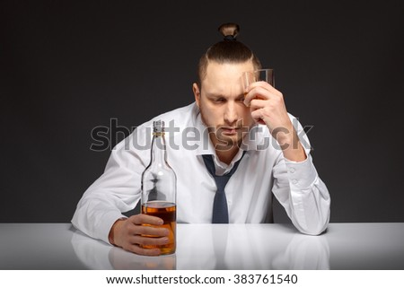 A young man in a white shirt sits at a table and suffers from a hangover Addicted to alcohol, alcoholism concept, social problem - stock photo
