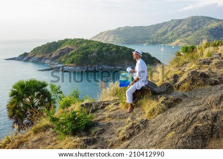 A young man in a white suit sitting on the beach with a map