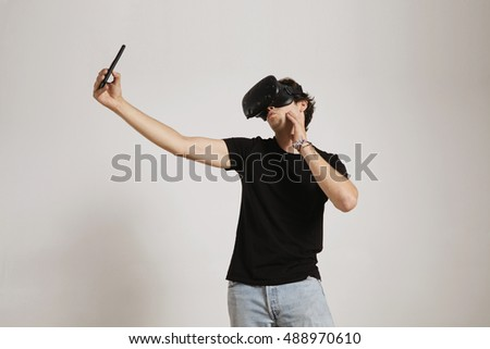 A young man in black t-shirt and jeans wearing a VR headset makes a duckface while taking a selfie with his smartphone, isolated on white
