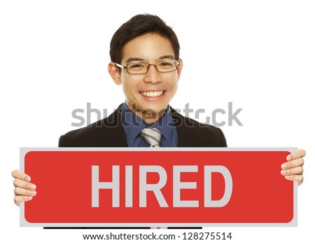 A young man in business attire holding a sign indicating hired - stock photo