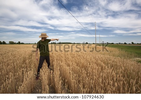 A young man in casual clothing standing in wheat field with straw hat on using two harnds to point that way. - stock photo