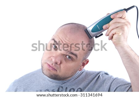 a young man in grey shirt  shaving his head with an electric razor isolated white