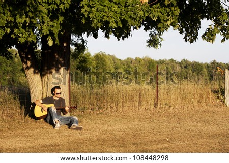 A young man in jeans, sunglasses and tshirt leaning against an old maple tree near a page wire fence playing guitar by himself at sunset. - stock photo