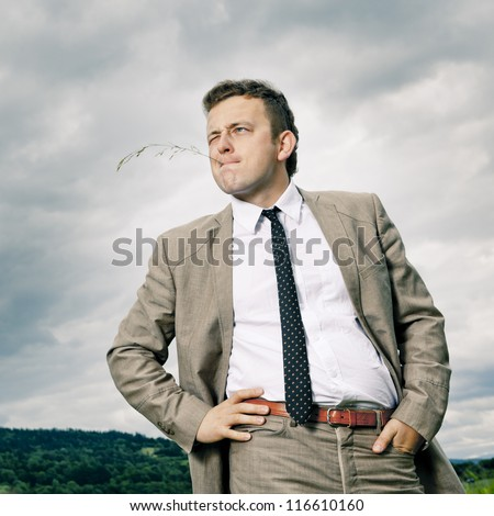 A young man in nature. Standing and thinking about something, staring into the distance. - stock photo