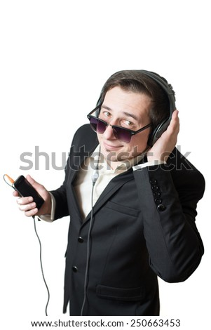 A young man in suit and glasses with headphones listening a music from cellphone isolated over the white background. Studio portrait of chilling office worker