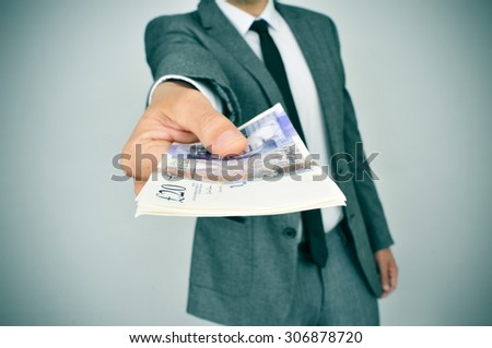 a young man in suit giving a wad of pound sterling bills to the observer - stock photo