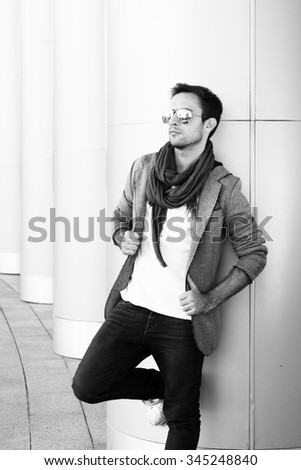 a young man in sunglasses, stylishly dressed on the modern building background. black and white