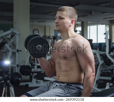 A young man in the gym performing an exercise one-arm dumbbell curl.
