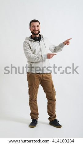 A young man in white hoody and khaki pants is smiling and pointing at something on his left - stock photo