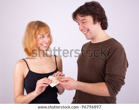 A young man is giving his girlfriend some money