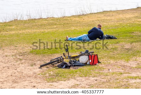 A young man is laying on grass besides water