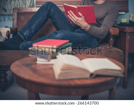 A young man is relaxing on a sofa at home and is reading a book - stock photo
