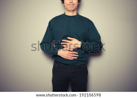 A young man is rubbing his stomach - stock photo