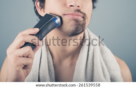 A young man is shaving off half of his beard - stock photo